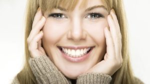 smiling-woman-with-hands-on-face